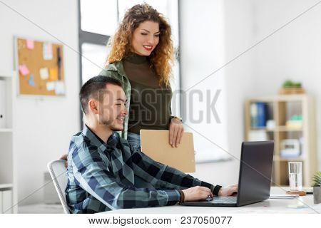 business, technology and people concept - happy creative team with laptop computer working at office