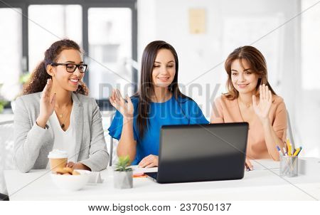business, technology and people concept - happy smiling businesswomen having video chat by laptop computer at office