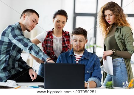 business, technology and people concept - creative team with laptop computer working at office