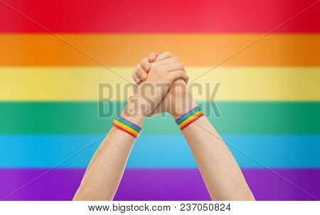 lgbt, same-sex relationships and homosexual concept - close up of male hands wearing gay pride awareness wristbands making winning gesture over rainbow background