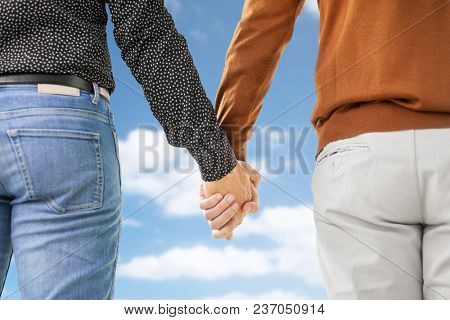same-sex relationships, lgbt and homosexual concept - close up of male gay couple holding hands over blue sky and clouds background