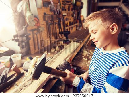 carpentry, woodwork, building and people concept - happy little boy with hammer hammering wood plank at workshop