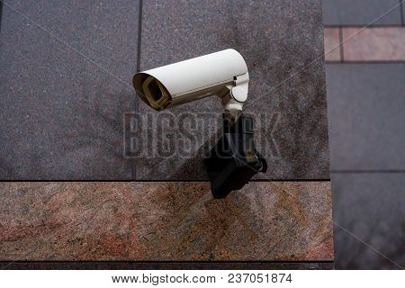 Surveillance Video Camera Is Mounted To A Brick Wall Outside A Building For Security.