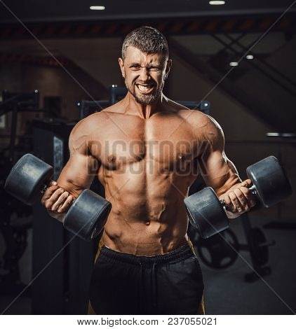 European Caucasian Athletic Man Bodybuilder Holding Dumbell And Showing His Muscular Arms. Man Doing