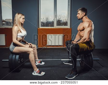 Athletic Man And Fitness Girl Are Sitting In Front Of Each Other On The Barbell Opposite Window. Lov