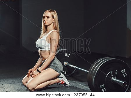 Athletic Sexy Blond Girl With A Perfect Figure In Shorts Siting On The Knees In Gym And Smiling. Whi