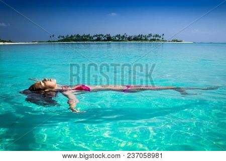Beautiful tanned woman relaxing on white sand at tropical island on Maldives.