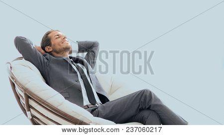 happy businessman relaxing in big comfortable armchair