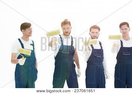 team of builders with paint rollers