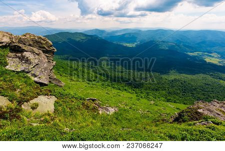 Rocky Cliff Over The Grassy Valley. Beautiful Summer Landscape With Mountain Ridge In The Distance