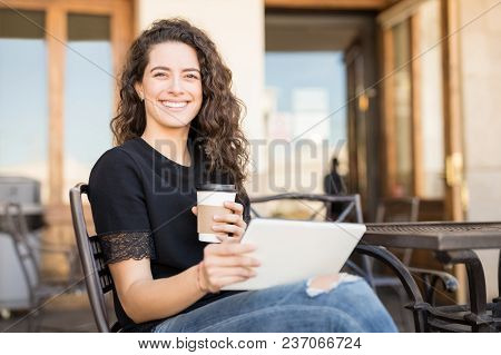 Beautiful Young Brunette Sitting At Outdoors Restaurant With Cup Of Coffee And Digital Tablet