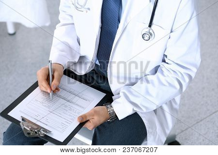 Doctor Man Filling Up Medical Form On Clipboard Closeup. Healthcare, Insurance And Medicine Concept.