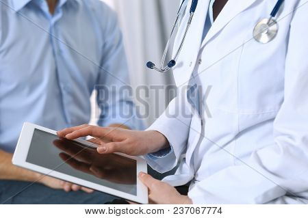 Female Doctor Using  Touchpad Or Tablet Computer While Consulting Man Patient In Hospital. Medicine