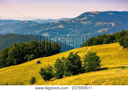 Wooden Shed On The Grassy Hillside. Beautiful Landscape With Krasna Mountain Ridge In The Distance I