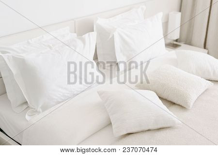 Comfortable Soft Pillows On The Bed. Close-up White Bedding Sheets And Pillow On Light Wall Room Bac