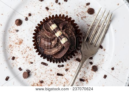 Chocolate Cupcake On White Plate With Fork, Dusted With Cocoa Powder And Chocolate Sprinkles, Overhe
