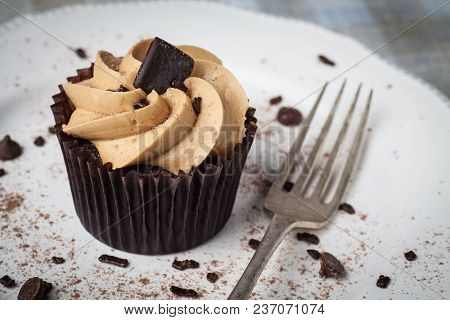 Salted Caramel Cupcake On White Plate With Fork, Dusted With Cocoa Powder And Chocolate Sprinkles