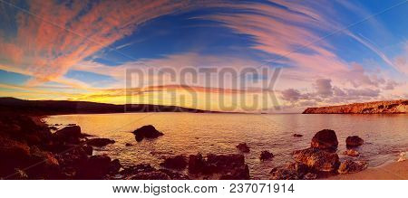 Cyprus Beautiful Sunrise At The Sea With Rocks And Cloudy Sky, Natural Panoramic Background. Summer