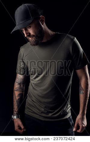 Pensive Black Bearded Male Dressed In A Grey Shirt, Sunglasses And Baseball Cap Posing Over Grey Bac