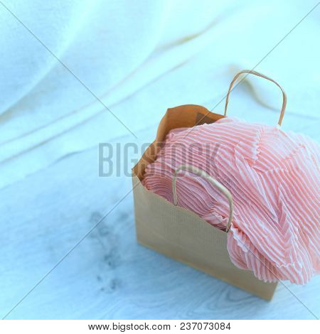 Toning A Paper Bag With Purchases On The Wooden Light Background. Light Pink Scarf In A Paper Bag Gi