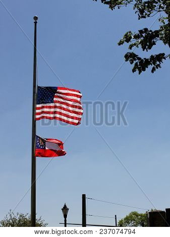 United States Flag And State Of Georgia Flag Flying At Half Mast.