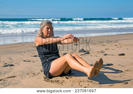 Sportive mature woman doing excercises at the beach at the atlantic ocean