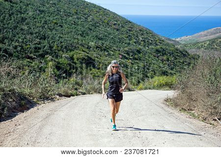 Sportive mature woman jogging uphill at the atlantic ocean