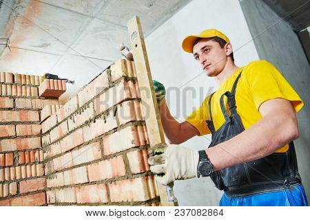 bricklaying. Worker checks erected brick wall with level