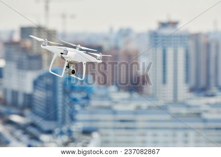 drone quadcopter with digital camera hovering over city