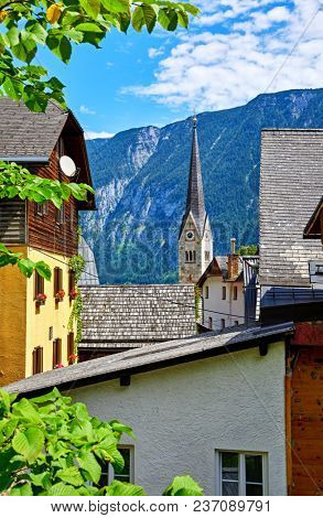 Hallstatt, Austria. Traditional houses and old roofs with view to mountains and broach of chapel of church at coast of lake Hallstattersee among austrian Alps.