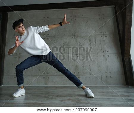 Teenage Boy In Jeans And Sneakers, White Sweater And Baseball Cap Dances Hip-hop In Dance Studio. Dy