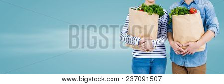 Couple mid sections with grocery bags against blurry blue background