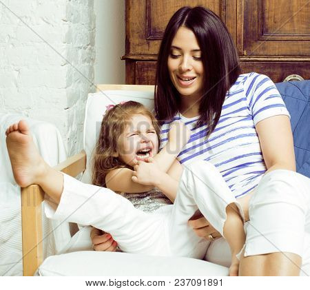 Portrait Of Mother And Daughter Laying In Bed And Smiling Close Up, Lifestyle Family People Concept