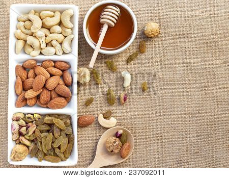 Dried Fruits And Variety Of Nuts In A Dish With Honey In A Bowl On The Wooden Table, Such As Figs, A