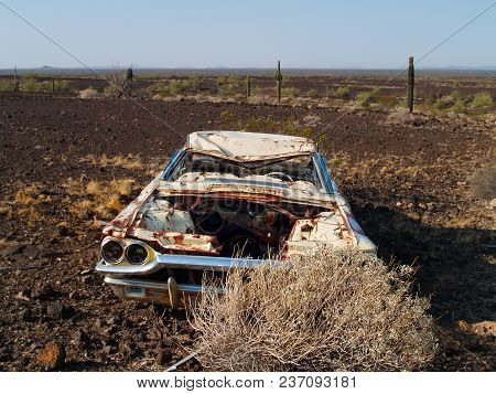 An Old Abandoned Car From The 1970s Lying Forgotten In The Vastness Of The Arizona Desert Near The T
