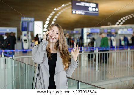 Woman Talking By Smartphone At Airport Hall, Wearing Grey Coat And Black Bag, Showing Ok. Concept Of
