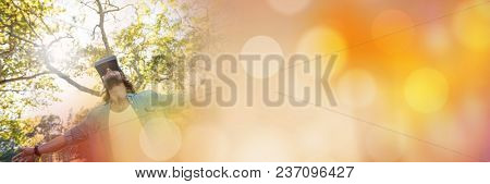 Low angle of man in virtual reality headset embracing forest with orange bokeh transition