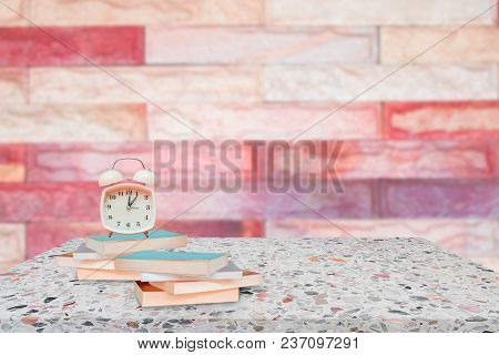 Alarm Clock And Books On Stone Shelf In Library School Concept With Brick Wall Blur Background Copy