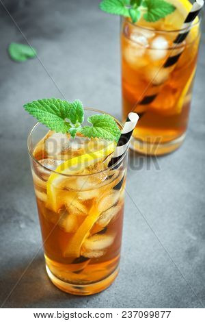 Iced Tea With Lemon, Mint And Ice Cubes Over Gray Concrete Background, Copy Space. Iced Cold Summer