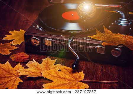 An Old Dusty Gramophone Playing A Vinyl Record At Autumn Time
