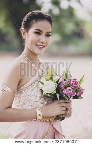 Portrait Of Asian Younger Woman Wearing Thai Tradition Clothes Holding Pink Lotus Flower In Hand Too