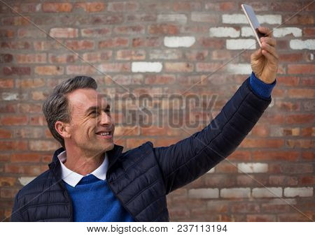 Man in coat taking selfie against red brick wall