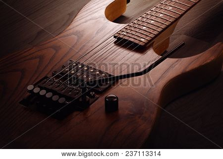 Close Up On The Body Of Custom Electric Guitar With Natural Finish, Selective Light On It, Wooden Ba