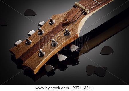 Close Up On The Headstock Of Custom Guitar, Black Picks Around, Glossy Background With Reflection