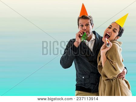 Couple with party hats against blurry blue background