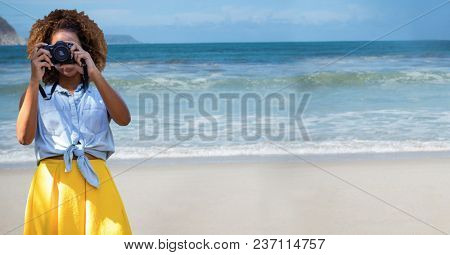 Millennial woman in summer clothes with camera against beach