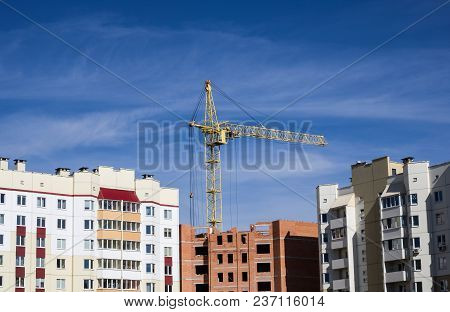 Construction Crane Above Tall Houses Against The Blue Sky, Building