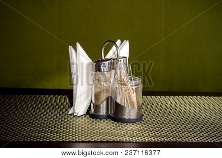 Pepper Shaker, Salt Shaker And Napkins On A Stand On A Table