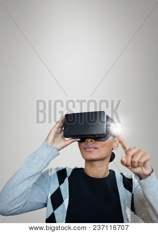 Woman in VR headset touching a flare against grey background