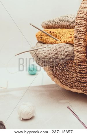 Stack Of Cozy Knitted Sweaters In A Wicker Basket